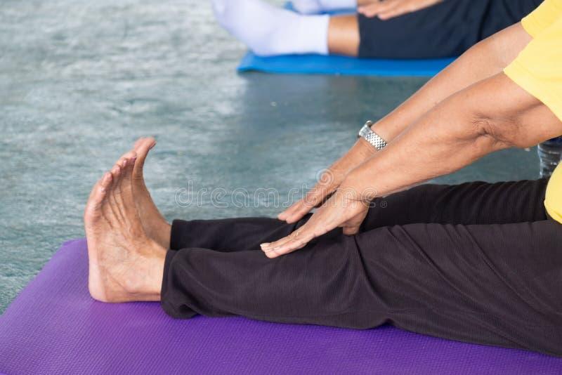 De bejaarden in een yoga oefenen houding uit royalty-vrije stock afbeeldingen