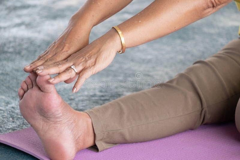 De bejaarden in een yoga oefenen houding uit royalty-vrije stock foto