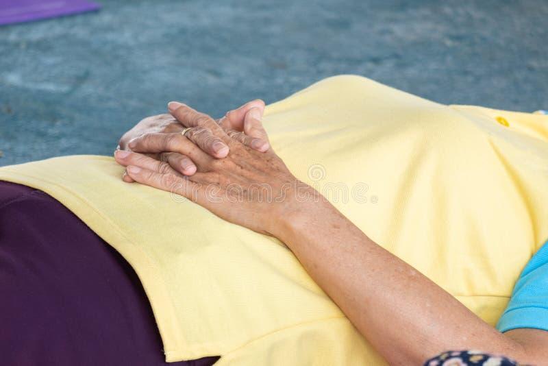De bejaarden in een yoga oefenen houding uit royalty-vrije stock foto's