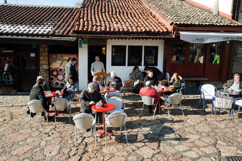 De bejaarden en andere mensen zitten bij koffielijsten aangaande de straat met historische gebouwen stock fotografie