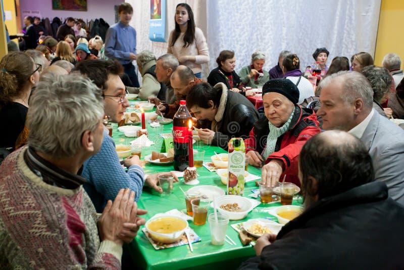 De bejaarden en de mensen hebben een voedsel bij het diner van de Kerstmisliefdadigheid voor de daklozen royalty-vrije stock foto's