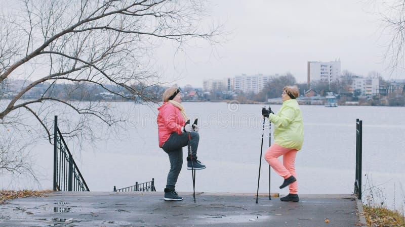 De bejaarden in de herfst parkeren het doen van opwarming vóór het noordse lopen stock fotografie
