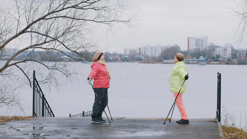 De bejaarden in de herfst parkeren het doen van opwarming vóór het noordse lopen royalty-vrije stock foto