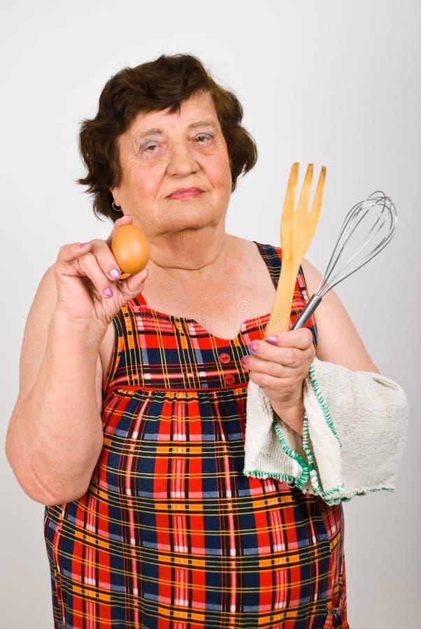 De bejaarden koken vrouw die ei toont stock foto