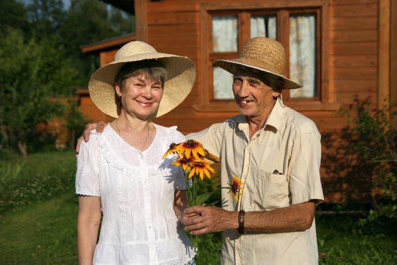 De bejaarden koppelen aan boeket van rudbeckiabloemen stock fotografie