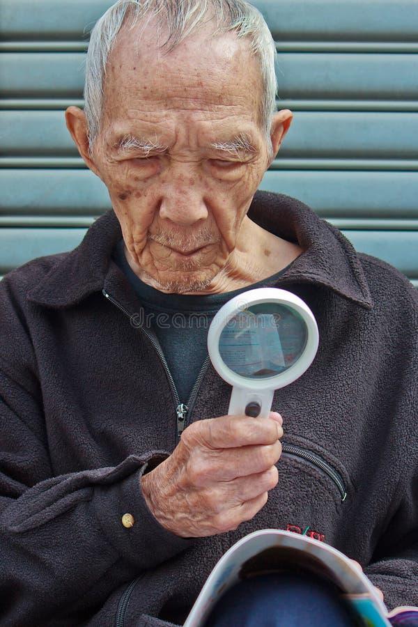 De bejaarden om met een vergrootglas te lezen stock fotografie