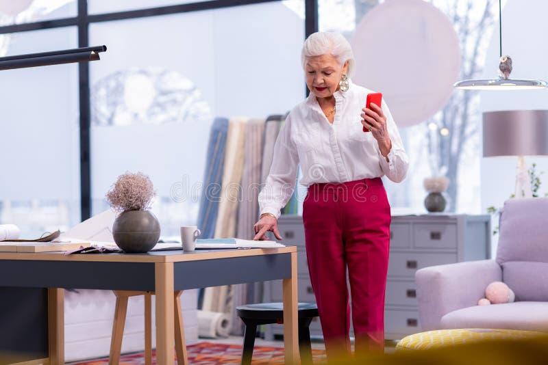 De bejaarden stellen zich onderneemster voor die zich in het bureau bevinden een telefoon houden royalty-vrije stock afbeelding