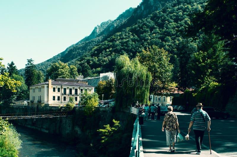 De bejaarden zijn op een steeg in een bergtoevlucht op een mooie de zomerdag Een mooie decoratie met een bergrivier en velen royalty-vrije stock fotografie
