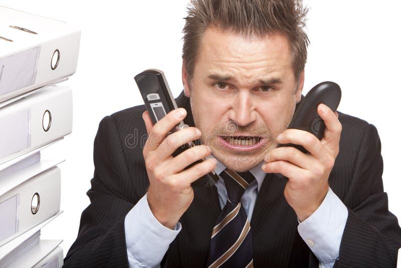 De beklemtoonde bedrijfsmens met telefoons schreeuwt royalty-vrije stock foto's