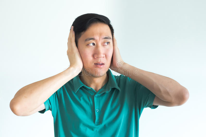 De beklemtoonde mens die zijn oren behandelen en wil niet horen, te luid ruchtbaar maken royalty-vrije stock afbeeldingen