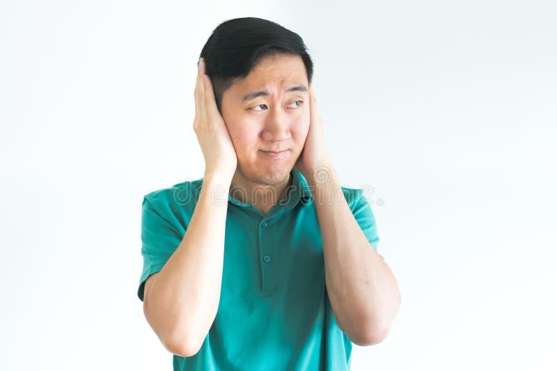 De beklemtoonde mens die zijn oren behandelen en wil niet horen, te luid ruchtbaar maken stock fotografie
