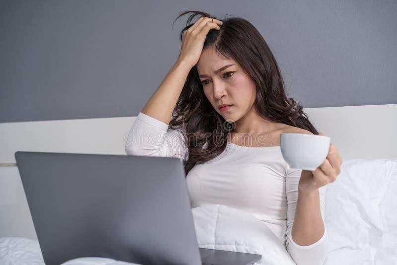 De beklemtoonde vrouw die een kop van koffie drinken en laptop met behulp van verwerkt gegevens stock foto