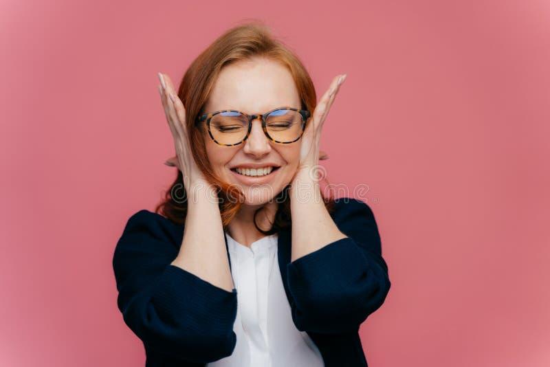De beklemtoonde vrouwelijke leraar behandelt oren, heeft hoofdpijn wegens lawaaierige leerlingen, dichtklemt tanden, negeert lawa royalty-vrije stock foto's