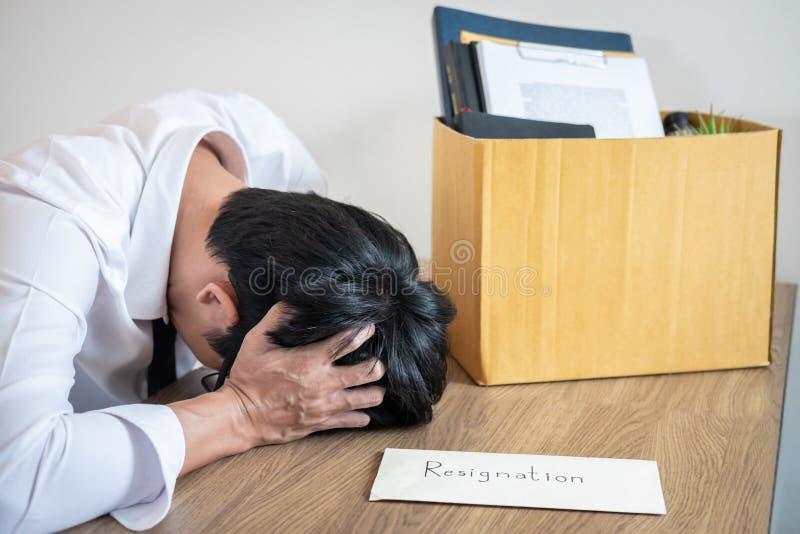 De beklemtoonde zakenman zal zijnd berusting en inpakkende bezittingenbedrijf en dossiers in bruin kartonvakje, die veranderen en stock afbeelding