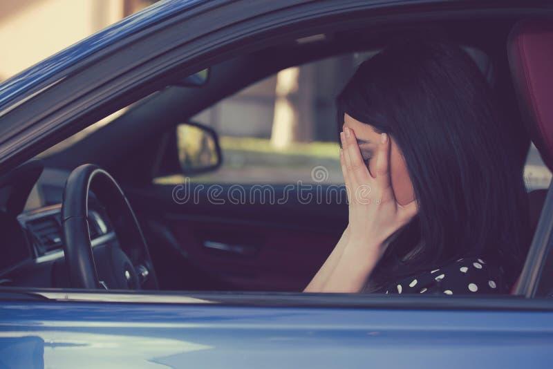 De beklemtoonde zitting van de vrouwenbestuurder binnen haar auto royalty-vrije stock afbeeldingen