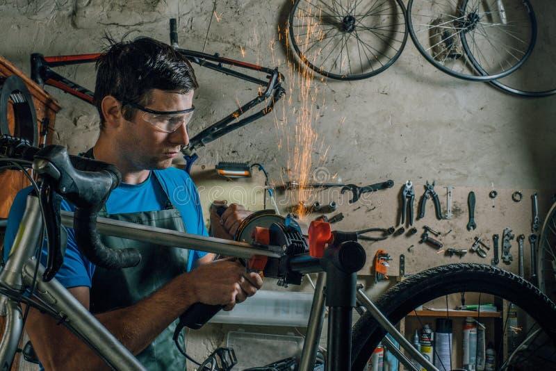 De bekwame fietswerktuigkundige in een workshop herstelt een fiets royalty-vrije stock foto's