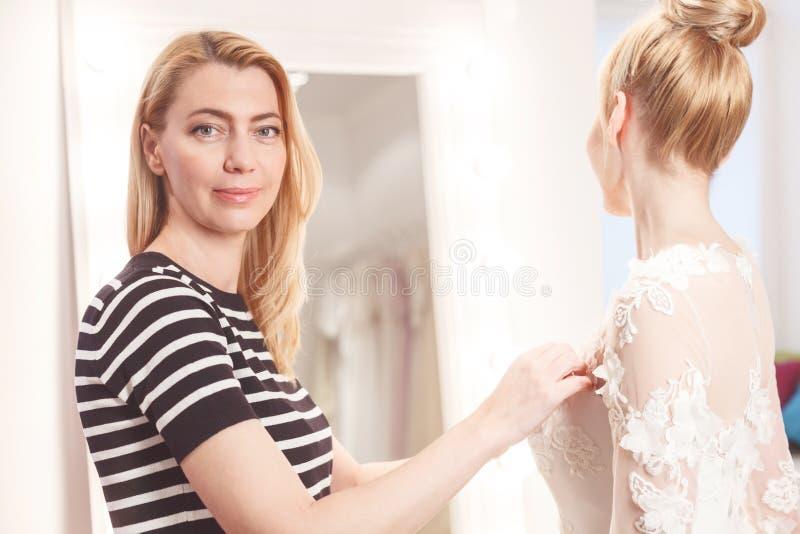 De bekwame verkoopster helpt toekomstige bruid royalty-vrije stock foto