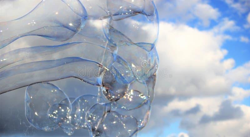 De bel borrelt drijvende zeepafwijking in blauwe hemel met wolken stock foto