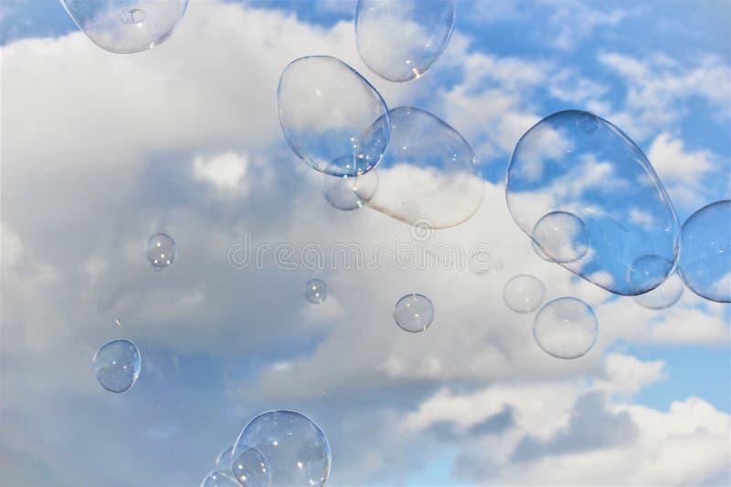 De bel borrelt drijvende zeepafwijking in blauwe hemel met wolken royalty-vrije stock fotografie