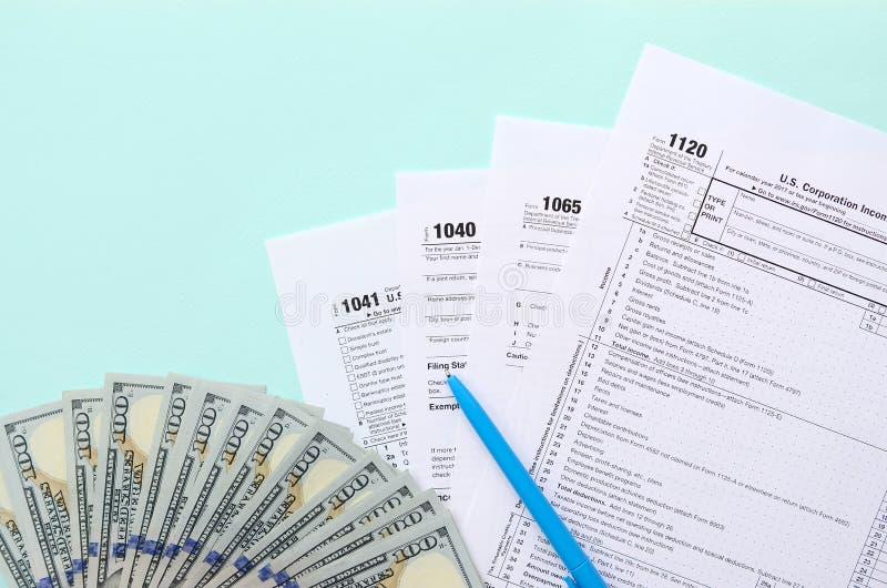 De belastingsvormen ligt dichtbij honderd dollarsrekeningen en blauwe pen op een lichtblauwe achtergrond Inkomensbelastingaangift royalty-vrije stock afbeelding
