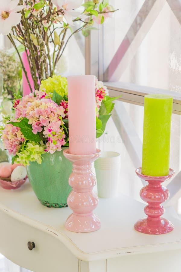 De belles fleurs roses dans un vase vert et des bougies sur le commode en bois blanc photographie stock libre de droits