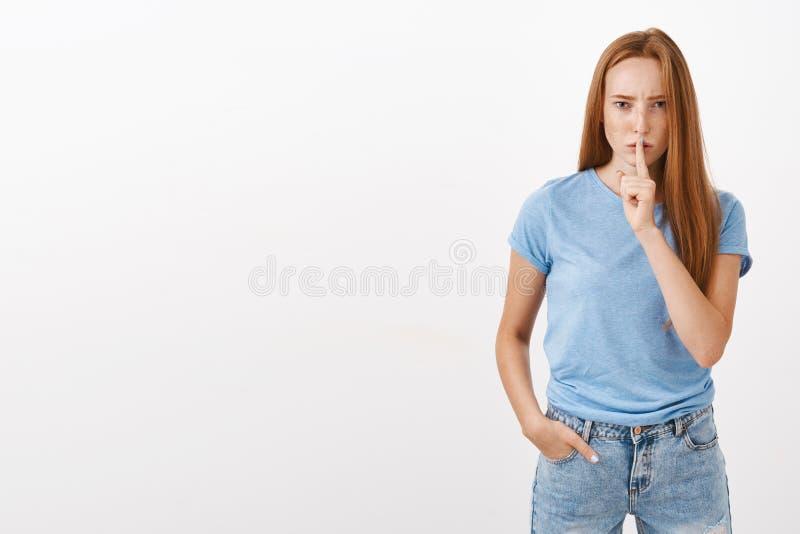 De belofte houdt mond gesloten Portret van ernstig-kijkt intense en bazige roodharigevrouw die met sproeten het doen zwijgen fron royalty-vrije stock afbeeldingen