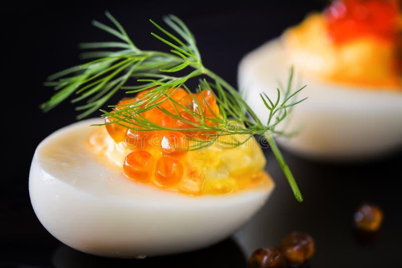 De bemande eieren met rode kaviaar versieren en dilledecoratie op dark royalty-vrije stock foto