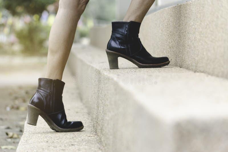 De benen die van close-upvrouwen omhoog stap in laarzen boven lopen aan royalty-vrije stock foto