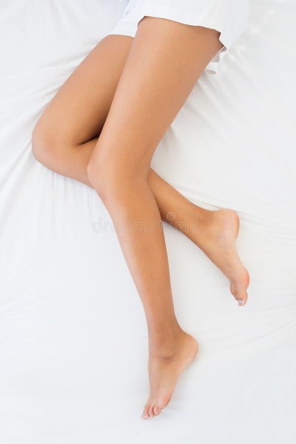 De benen die van de slanke vrouw op bed liggen royalty-vrije stock afbeeldingen