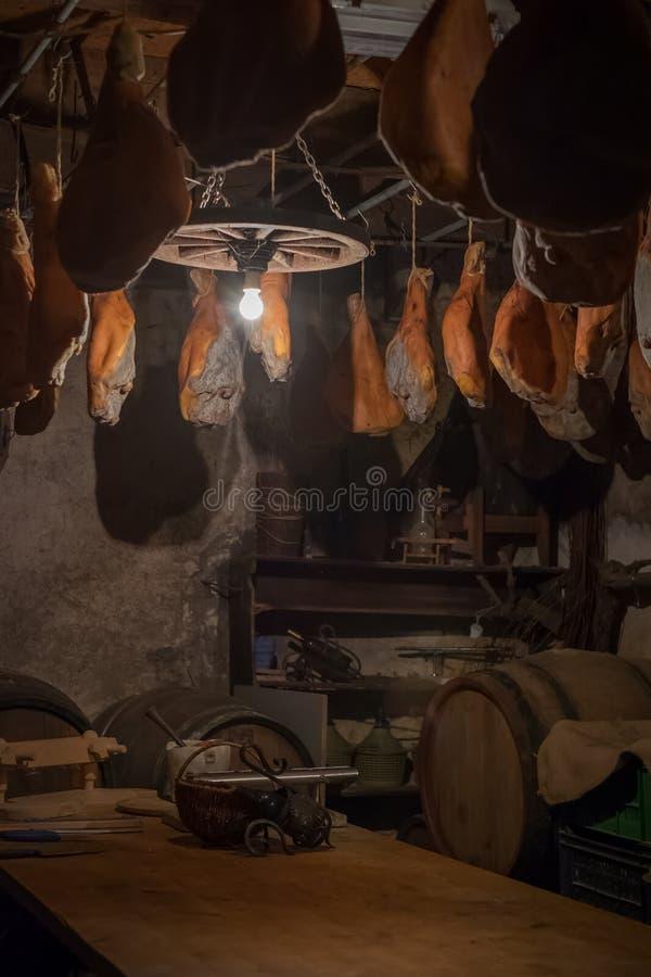De benen die van het Prosciuttovarkensvlees in de kelderverdieping hangen Traditionele ham in Slovenië stock afbeelding