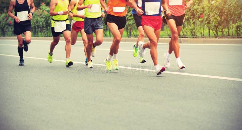 De benen die van marathonatleten op stadsweg lopen royalty-vrije stock fotografie