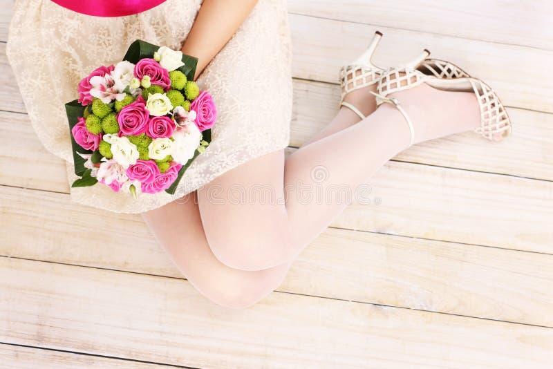 De benen en de bloemen van de bruid op houten vloer stock foto's