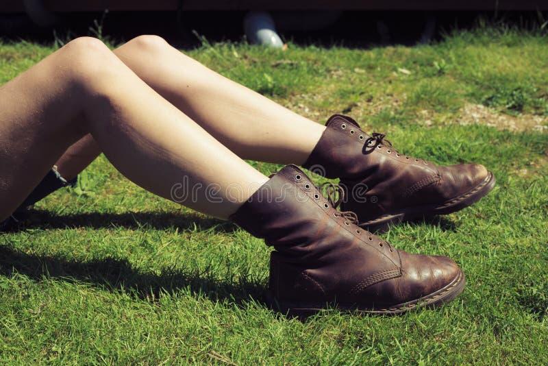 De benen en de voeten van de jonge vrouw op het gras royalty-vrije stock afbeelding