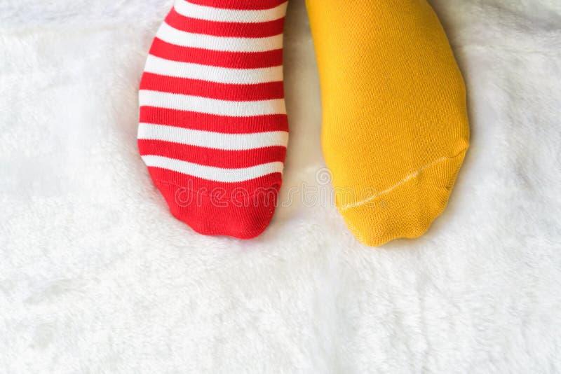 De benen in sokken twee kleuren wisselen, Rode en gele zijtribune op witte stoffenvloer af stock afbeeldingen