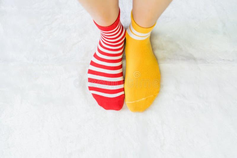 De benen in sokken twee kleuren wisselen, Rode en gele zijtribune op witte stoffenvloer af stock foto