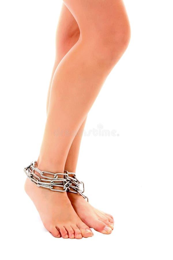 De benen van de vrouw die door geïsoleerde ketting worden verbonden stock afbeelding