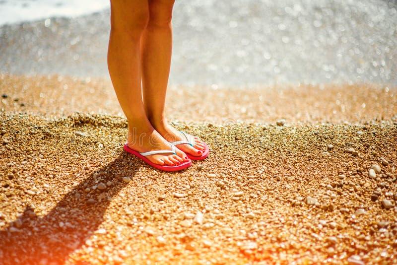 De benen van de vrouw in pantoffels op het strand stock fotografie