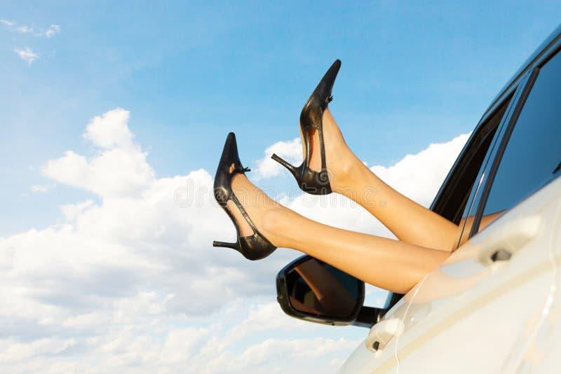 De benen van de vrouw uit autoraam stock foto