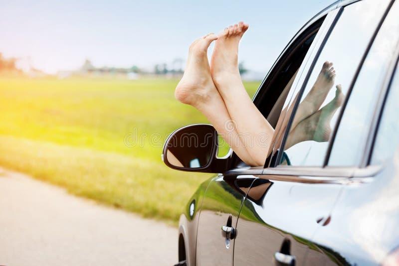 De benen van de vrouw uit het autoraam stock afbeelding