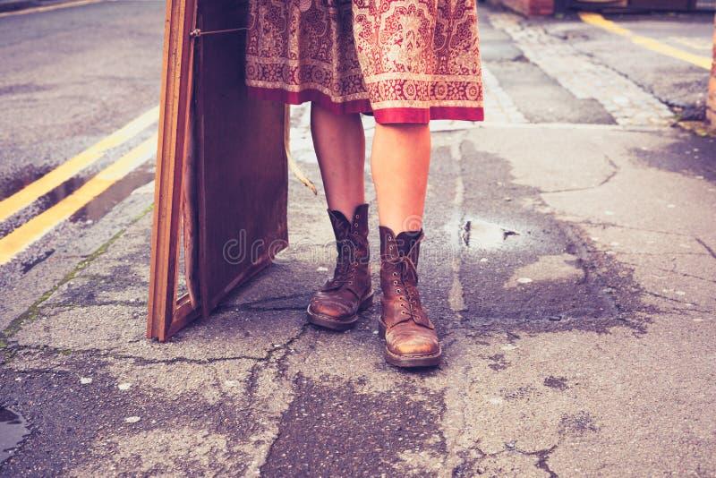 De benen van een jonge vrouw die zich in de straat met beeld bevinden royalty-vrije stock foto