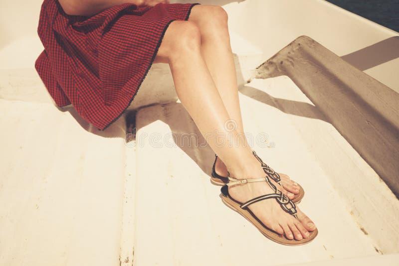 De benen van een jonge vrouw in een boot royalty-vrije stock foto