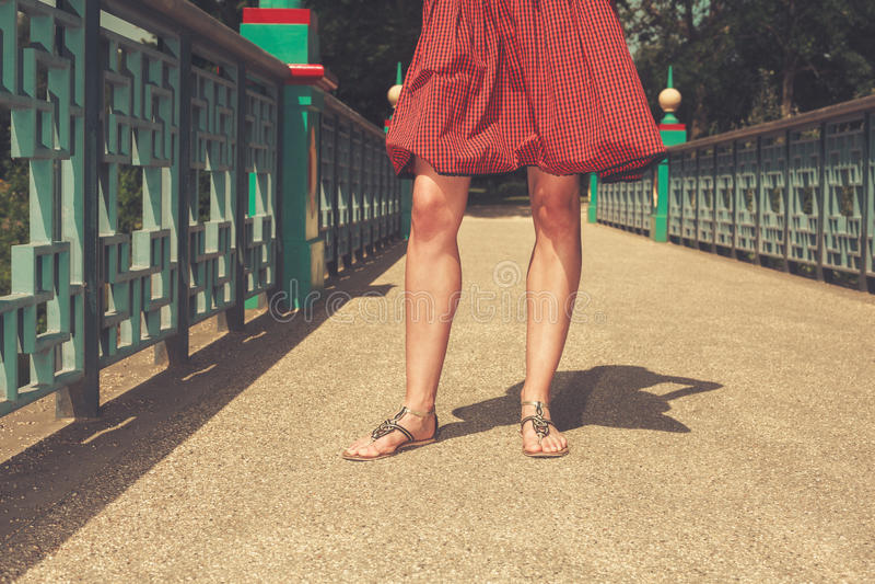 De benen van een jonge vrouw op een brug stock afbeeldingen