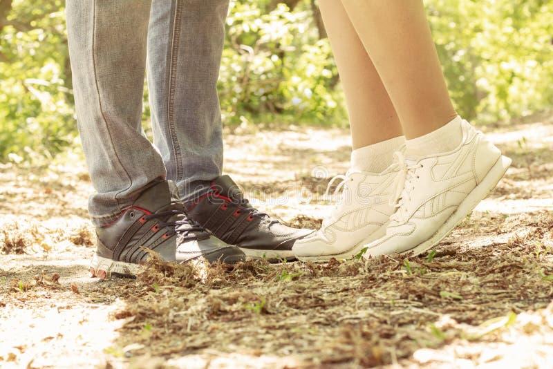 De benen van een kerel en een meisje zij meisje kussen is op haar sokken stock afbeelding