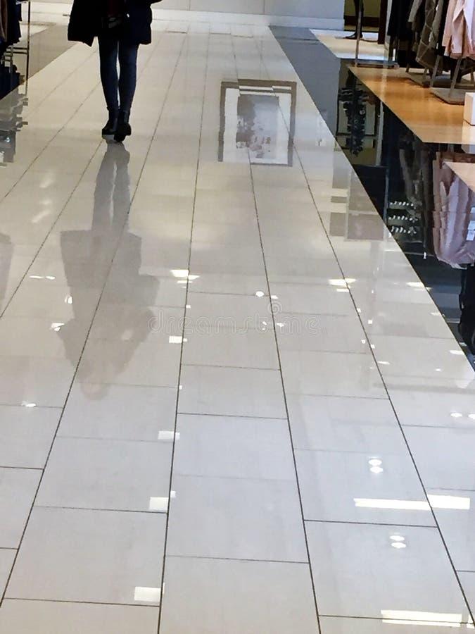 De benen van een klant denken van de glanzende betegelde vloer van het winkelen na stock fotografie