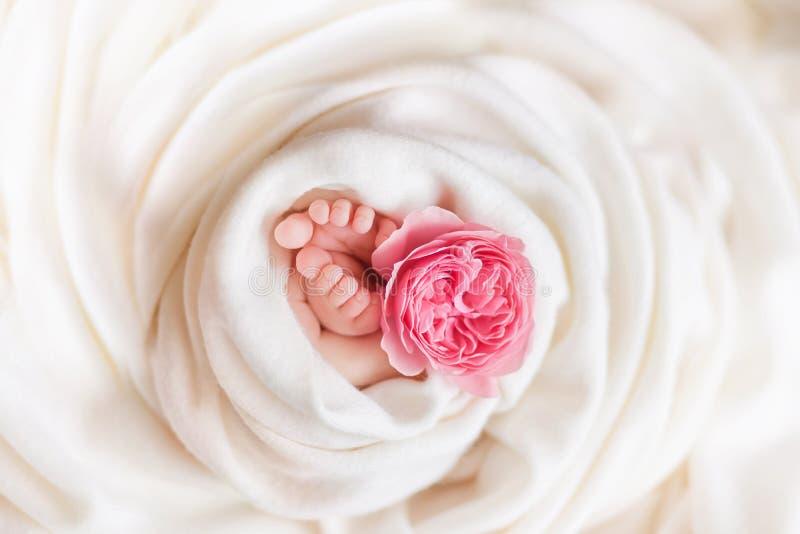 De benen van een pasgeboren meisje met namen op een witte achtergrond toe stock foto