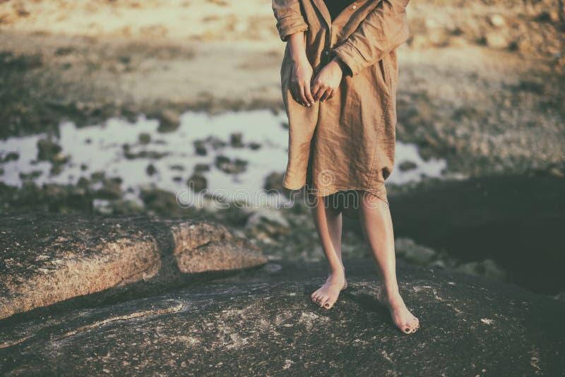 De benen van een vrouw terwijl status op de rots door het strand stock foto
