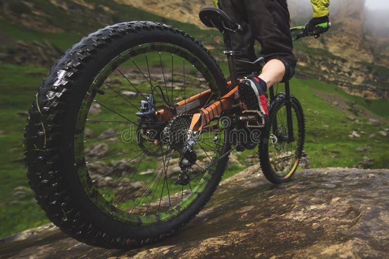 De benen van fietser en achtergedeelte rijden close-upmening van achtermtbfiets in bergen tegen achtergrond van rotsen in mistig stock foto