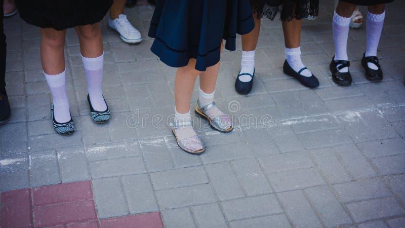 De benen van het babymeisje in wit golf en de mooie schoenen zijn in de opstelling op de schoollijn op 1 September 1 september -  royalty-vrije stock afbeelding