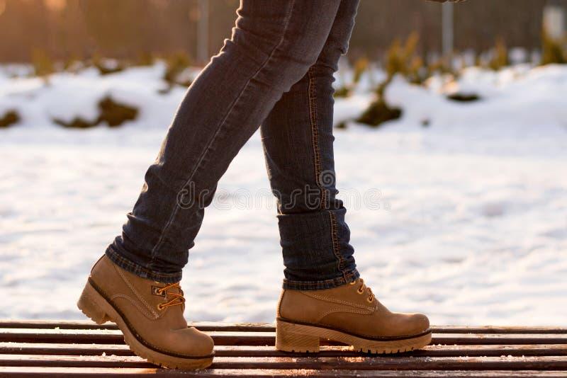 De benen van het close-upmeisje in jeans in beige laarzen die zich op houten bank in de winter ijzige zonnige dag op vage achterg stock afbeelding