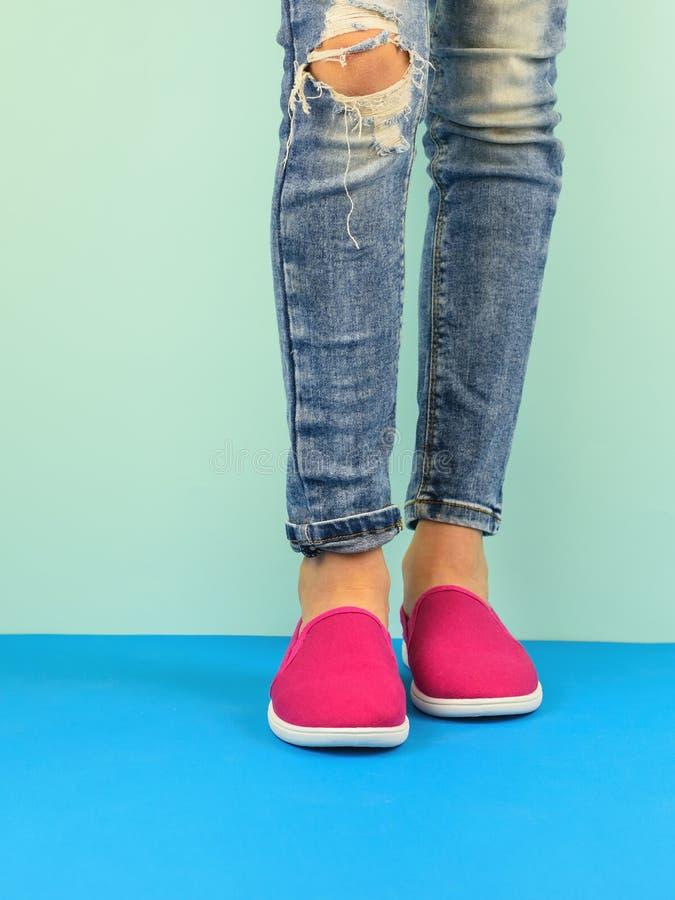 De benen van het Hipstermeisje ` s in gescheurde jeans op de blauwe vloer door de blauwe muur Moderne stijl stock foto's